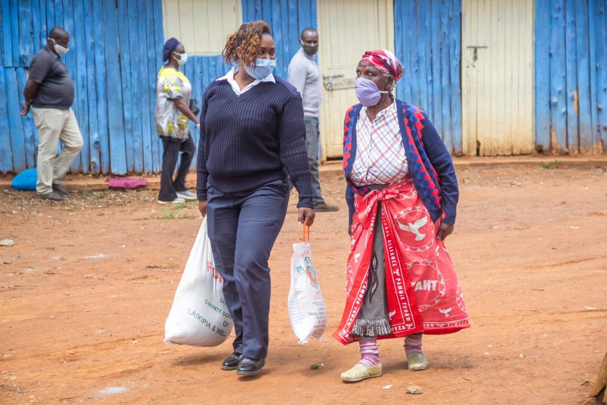 Silvia Wanza, a police officer at Nanyuki Police Station assists Veronica Njogu, a beneficiary of the Lisha Jamii Initiative to carry her care package